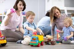 Mödrar med deras behandla som ett barn lekleksaker i daycaremitt royaltyfri bild