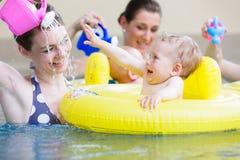 Mödrar och ungar som har gyckel som spelar tillsammans med leksaker i pöl fotografering för bildbyråer