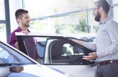 Möglicher Käufer, der mit einem Autohändler nahe bei einem Auto spricht lizenzfreies stockbild