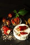 Möglig ost och peppar på en svart bakgrund chili torkade peppar Kryddig möglig ost royaltyfria bilder