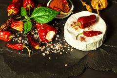 Möglig ost och peppar på en svart bakgrund chili torkade peppar Kryddig möglig ost royaltyfri bild