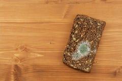 Mögligt bröd i trätabell sjuklig mat spolierad mat Royaltyfri Foto