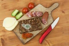 Mögligt bröd i trätabell sjuklig mat spolierad mat Arkivfoton