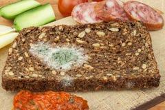 Mögligt bröd i trätabell sjuklig mat spolierad mat Arkivfoto