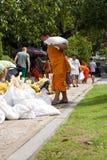 Mönch, der Sandsäcke holt, um Überschwemmung zu verhindern   lizenzfreies stockbild