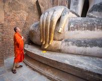 Mönch, der vor großer Buddha-Statue in Wat Si Chum, historischer Park Sukhothai, Thailand betet stockfotografie