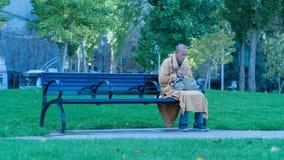 Mönch Praying auf einer Bank Stockbild