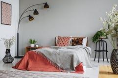 Mönstrad kudde och grå filt på konungformatsäng med mörkt - orange duntäcke i det lyxiga sovrummet som är inre i elegant lägenhet royaltyfria foton