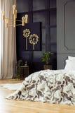 Mönstrad säng i grå sovruminre med den guld- ljuskronan, den svarta affischen och växter royaltyfri fotografi