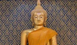 Mönstrar den guld- statyn för Buddha på guld- och blå bakgrund Thaila Arkivfoton