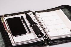 Mörda planläggningsbegreppet - kalender, mobiltelefon och kniv Arkivfoto