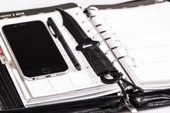 Mörda planläggningsbegreppet - kalender, mobiltelefon och kniv Arkivbilder