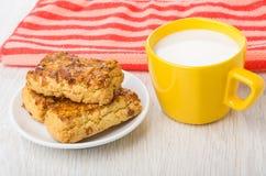 Mördegskakakakor med jordnötter i tefat, mjölkar, den röda servetten Arkivfoton