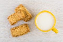 Mördegskakakakor med sesam och mjölkar i gul kopp Royaltyfri Bild