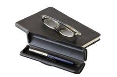 Mörk anteckningsbok, exponeringsglas och penna Fotografering för Bildbyråer