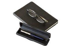 Mörk anteckningsbok, exponeringsglas och penna Arkivfoton
