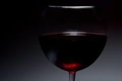 Mörk atmosfärisk bild av rött vin i ett exponeringsglas Royaltyfri Fotografi