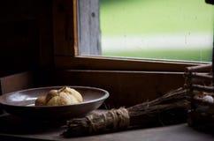 Mörk bild av ljus som flödar in på bröd och päronet i bunke förbi fönsterfönsterbrädan Arkivfoton