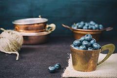 Mörk bild för blåbär Nya frukter, bär i en gammal kopparkopp Ökat oväsen, film imiterar fotografi arkivfoto