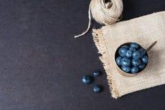 Mörk bild för nya blåbär med kopieringsutrymme på vänstersida Nya frukter, bär i en gammal kopparkopp, bunke Mörker utformat mate arkivfoto