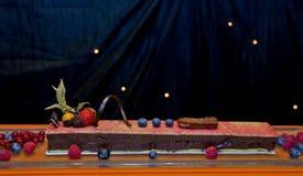 Mörk chokladkaka med toppning för ny frukt och runt om skärm Arkivfoto