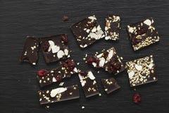Mörk chokladstång med bär, pistascher och mandeln på svart bakgrund royaltyfri fotografi