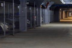 Mörk coridor i det underjordiska parkera garaget med separata askar, sikt på utfarten royaltyfria bilder
