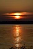 Mörk guld- sjösolnedgång med solen som döljas delvist Arkivfoto