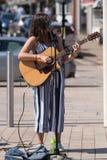 Mörk haired kvinnlig sångare på gatan med solglasögon och royaltyfria bilder