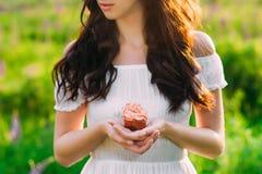 Mörk haired ung flicka som rymmer enlagad mat med grädde muffin royaltyfri foto