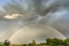 Mörk himmel med den dubbla regnbågen royaltyfri fotografi