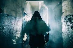 Mörk kontur av den konstiga faramannen i huv i tillbaka ljus med rök eller dimma i läskig grungekorridor eller tunnel arkivbilder