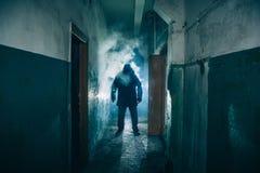 Mörk kontur av den konstiga faramannen i huv i tillbaka ljus med rök eller dimma i läskig grungekorridor eller tunnel fotografering för bildbyråer