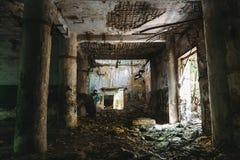 Mörk korridor av den förstörda övergav fabriken med kolonner Royaltyfri Bild