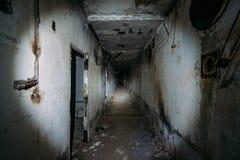 Mörk kuslig korridor i övergiven kärnkraftverk i Krim Första personsikt som går med ficklampan i smutsig grungetunnel royaltyfri bild