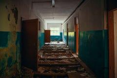 Mörk kuslig korridor med dörrar och brutet golv i gammal läskig övergiven byggnad, tunnelsikt arkivbild