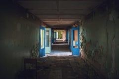Mörk kuslig korridor med dörrar och brutet golv i gammal läskig övergiven byggnad, tunnelsikt royaltyfria foton