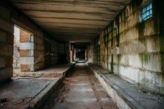 Mörk läskig korridor i den övergav industriella förstörda tegelstenfabriken, kuslig inre royaltyfri bild
