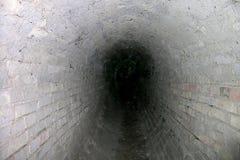 Mörk lång tunnel för tegelsten inom Arkivbild