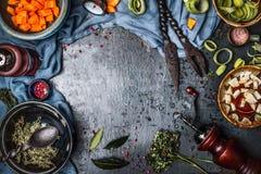 Mörk lantlig vegetarisk matbakgrund med bunkar av högg av grönsaker och smaktillsatsingredienser och kökhjälpmedel, bästa sikt, f Arkivbild