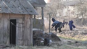 Mörk linne torkas på ett rep i vinden i byn stock video