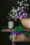 Mörk lynnestilleben med lösa blommor och en kopp på en tappningtabell arkivfoton