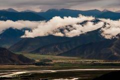 Mörk lynnig landskapsikt av berg och kullar i Tibet royaltyfri bild