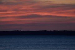 Mörk mångfärgad solnedgång på den blåa sjön Royaltyfria Foton