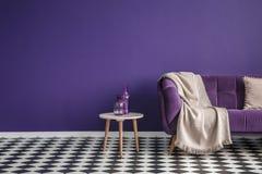 Mörk purpurfärgad soffa med en filt bredvid en liten tabell med flaskan royaltyfria bilder