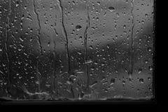 Mörk regndroppe för bakgrund på grå färger för fönsterexponeringsglas royaltyfri foto