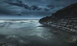 Mörk skymning fördunklar över havet Arkivbilder