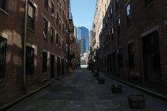 Mörk smal stadsgata Arkivfoto