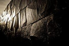 Mörk stenvägg som skiner med ljuset Arkivfoton