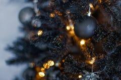 Mörk suddig bakgrund för jul med en svart julgran, prydnader och bokehljus royaltyfri fotografi